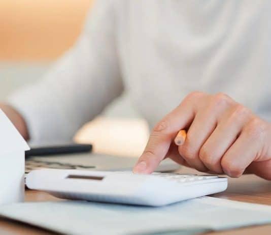 Homme avec une calculatrice et une mini maison